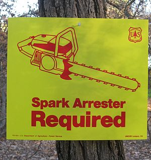 "Spark arrestor - A United States Forest Service ""Spark Arrester Required"" sign posted in a woodcutting area"