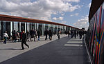 People walking over the Olympic bridge over Stratford Regional railway station.