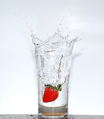 English: A strawberry falling into a glass of ...