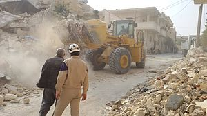 White Helmets (Syrian Civil War) - SCD clearing rubble following an attack in Maarat al-Nu'man in November 2014, using a USAID supplied bucket loader