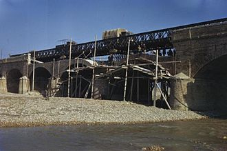 Bailey bridge - Allied military traffic crosses a Bailey bridge, spanning a damaged section of a masonry arch bridge. At the same time, local workers are rebuilding the original bridge. Italy 1944