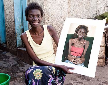 Picture of Concillia Muhau, who is featured in the film, holding an earlier picture of herself