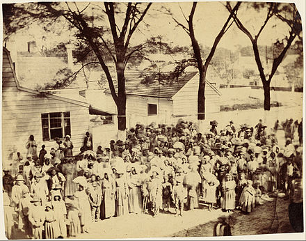 Slaves on J. J. Smith's cotton plantation near Beaufort, South Carolina, photographed by Timothy O'Sullivan standing before their quarters in 1862 Timothy H. O'Sullivan (American - Slaves, J. J. Smith's Plantation, South Carolina - Google Art Project.jpg