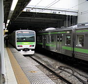 A Yamanote Line E231 series EMU on the left departs with a 205 series on the right