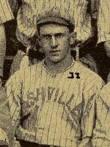 "A man wearing a light colored cap and baseball jersey with pinstripes with ""Nashville"" written across the chest."