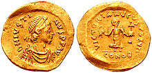 A golden coin showing the bust of Justin I along with its reverse, which depicts victory holding a globus cruciger.