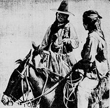 Black and white image of two men on horse back