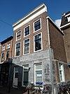 foto van Groot pand met de nok loodrecht op de straat, bestaande uit twee bouwlagen en een kelder