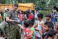 US Navy 060220-M-4855P-002 U.S. Marines assigned Company G, 2nd Battalion, 5th Marine Regiment, give candy to the local children before heading out to search through rubble in an effort to search for survivors.jpg
