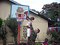 US Navy 071110-G-1959A-002 Navy Lt. Cmdr. Brad Fagan, assigned to U.S. Southern Command, lifts a small child up for a slam dunk at the Mercy ^ Sharing Foundation Orphanage.jpg