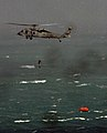 US Navy 071223-N-1688B-043 A Navy Search and Rescue swimmer descends from an MH-60S Seahawk helicopter to retrieve survivors from a life raft at sea.jpg