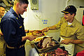 US Navy 081127-N-5758H-682 Cmdr. Don Gabrielson places a turkey leg on Chief Gas Turbine Electrician Raymond Quezada's plate.jpg