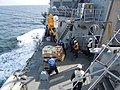 US Navy 110322-N-0775E-003 Sailors aboard the guided-missile destroyer USS Mustin (DDG 89) receive pallets of supplies during a replenishment at se.jpg