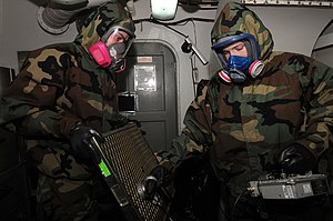 Radiation monitoring - Personnel wearing full protective gear while checking air filters for radioactive contamination
