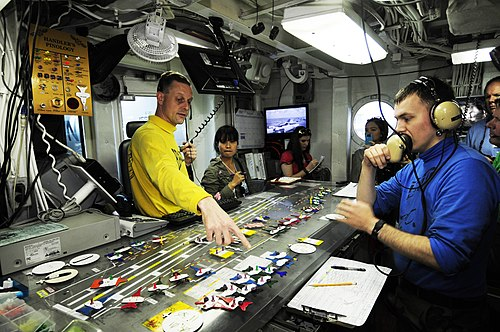 US Navy 110813-N-JO245-024 Lt. Cmdr Eric Harrington shows distinguished visitors from Vietnam the Ouija board in flight deck control aboard the air