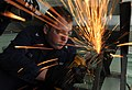 US Navy 111206-N-EK905-066 Hull Maintenance Technician 3rd Class Nicholas Pitzer grinds the frame of a table in the recreation room aboard the amph.jpg