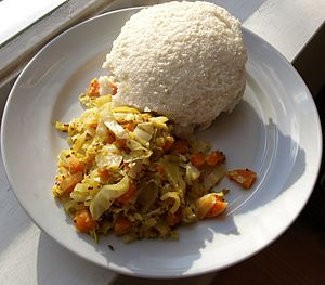 Ugandan cuisine - Ugali (top) and cabbage. It is more typically eaten with kale (Sukuma wiki).