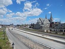 Una carretera, en construcción, atraviesa la foto de arriba a la izquierda a abajo a la derecha.  Junto a la carretera hay una gran iglesia y algunos edificios a la derecha.