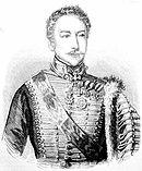 Black and white print shows a mustachioed man in an 1800s hussar uniform. The front of the jacket has lace arranged horizontally and there are a number of awards pinned to the left shoulder.