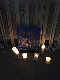 "Candles surround a sign that says ""Pray for our city"". The sign's painted background is a starry night sky with some buildings."