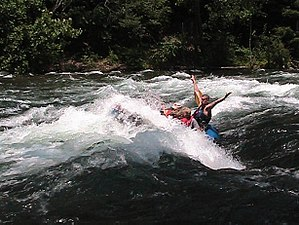 "Elizabethton, Tennessee - Raft guide plunging whitewater rafters downstream through ""The Big Hole"" in the Bee Cliff Rapids"