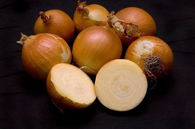 Six uncut onions and another one cut in half to show the layers