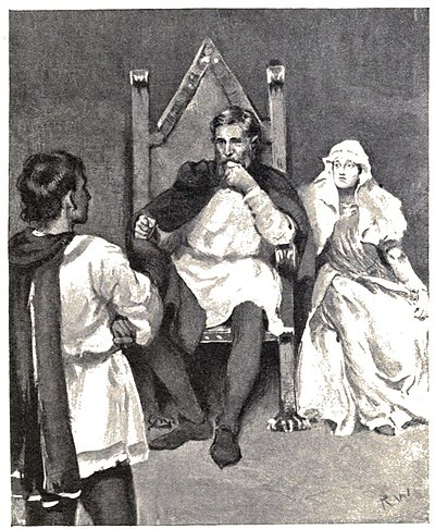 A man sitting on a large chair, a woman sitting beside him and another man standing in the foreground—in front of the sitting pair with his back to the viewer.