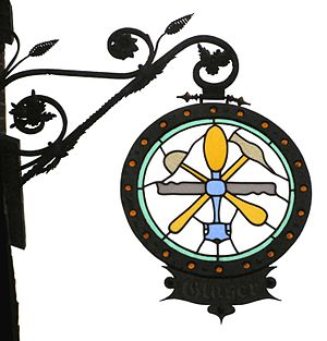 Traditional wrought-iron guild sign of a glazi...