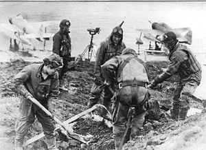 Nakajima A6M2-N - Japanese pilots at an A6M2-N plane anchorage. Two Rufe planes are visible in the background.
