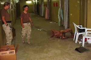Abu Ghraib torture and prisoner abuse - Lynndie England pulls a leash attached to the neck of a prisoner, who is forced to crawl on the floor, while Megan Ambuhl watches.
