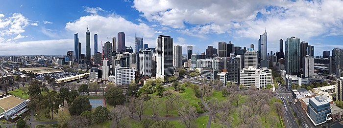 Panorama of city with park trees in foreground and many multi-storey buildings on the horizon
