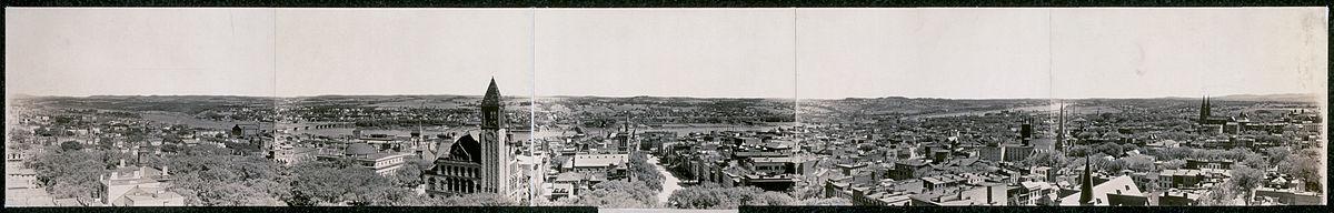 Um panorama de 1909, em sépia, mostra uma vista da cidade perpendicular ao rio;  há várias torres de igrejas e a torre da prefeitura pode ser vista à esquerda do centro.