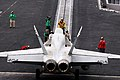 An F A-18E Super Hornet is directed onto a catapult aboard USS Ronald Reagan (5958098880).jpg