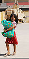 An Iraqi girl carries a bag of food she received from Iraqi Police (IP) officers during an IP-led humanitarian assistance event Aug. 29, 2010, at the Anbar business center in Ramadi, Anbar province, Iraq 100829-A-CE832-012.jpg
