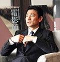 Un Andy Lau à l'air sérieux, assis et vêtu d'un costume
