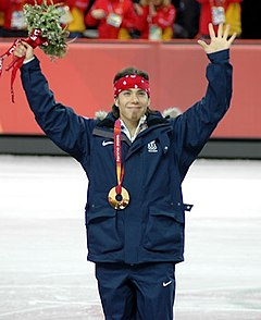 A man wearing a gold medal smiles with his arms raised above his head holding a flower bouquet in his left hand while wearing a dark blue tracksuit and a red bandanna on his head. There is a portion of the ice-rink in the background.