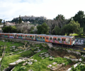 Athens Metro passes Acropolis near Thissio station in Athens Greece.png