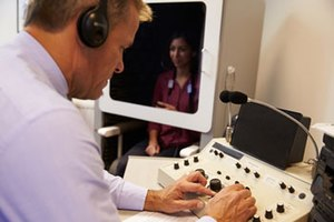 Image showing an audiologist testing the hearing of a patient inside a hearing booth and using an audiometer