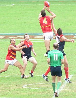 Ruckman (Australian rules football) - In this ruck contest during a 2006 Australian Football League match, Matthew Clarke of the Adelaide Football Club taps the ball to his fellow midfielders whilst leaping over Melbourne Football Club opponent Mark Jamar. The field umpire in the green uniform, Scott McLaren, is backing away from the contest after conducting the centre bounce.