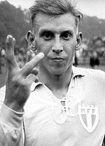 A blonde man raises his right hand to the camera with three fingers up; he is dressed in a light-coloured football kit.