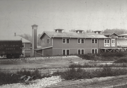 Long, two-story building next to a railroad