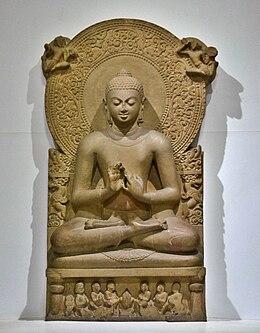Statua di Gautama Buddha con dharmachakra, mudrā e padmasana. La testa è circondata dall'aureola (sans. prabhā), un prestito della cultura greco battriana come la protuberanza cranica (sans. uṣṇīṣa) Nel registro in basso i pañcavaggiyā, la ruota del dharma e i cerbiatti, che identificano la predicazione del primo sutra a Sarnath. Epoca Gupta, museo di Sarnath