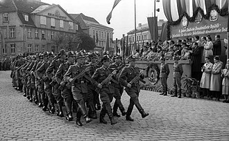 Volkspolizei - Members of the East German Volkspolizei parading through the streets of Neustrelitz in 1955. They are armed with World War II German StG 44 rifles.