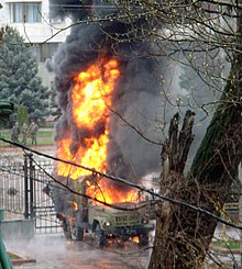 A military vehicle burning in front of gates in the background with a tree in the foreground.