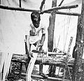 COLLECTIE TROPENMUSEUM Een man bewerkt de stammen van Manilla-hennep TMnr 10011401.jpg