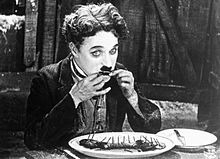 Chaplin, assis à table, mangeant un bout de sa chaussure.