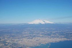 An aerial view of the Metropolitan City around Catania. Mount Etna is the peak at a distance.