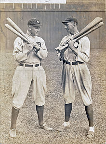 Two batters holding bats, conversing.