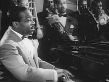 Cropped screenshot of Count Basie from the film Stage Door Canteen.