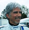 Damon Hill sporting a goatee in white racing overalls smiling to the left of the camera